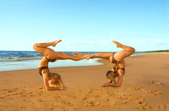 Two acrobatic girl on the beach. Two acrobatic girl doing trics on the beach Royalty Free Stock Photo