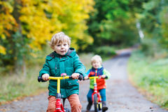 Two active brother boys driving on bikes in autumn forest Royalty Free Stock Image