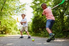Two active children making sport. Playing street hockey in the park stock photography