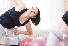Two Active Fitness Girls Exercising With Barbells indoors in Gym. Class.Horizontal Image Composition royalty free stock images