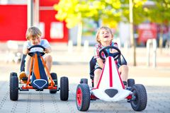 Two active little kid boys driving pedal race car in summer garden, outdoors. Children, best friends racing with fast stock photos