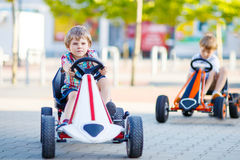 Two active little kid boys driving pedal race car in summer garden, outdoors. Royalty Free Stock Image