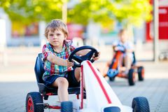 Two active little kid boys driving pedal race car in summer Stock Image