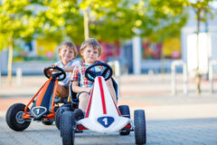 Two active little kid boys driving pedal race cars Stock Image
