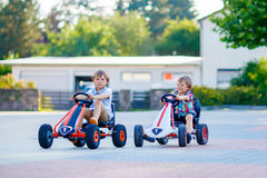 Two active little kid boys driving pedal race cars Stock Photos