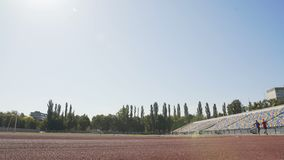 Two active runners competing at stadium, training hard to achieve sport success stock video