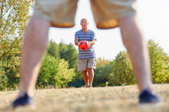 Two active senior men playing soccer. In the park Stock Photography