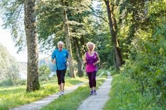 Two active seniors with a healthy lifestyle smiling while joggin. Full length front view of two active seniors with a healthy lifestyle smiling while jogging royalty free stock photos