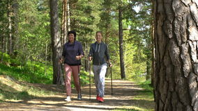 Two active women do Nordic walking in the Park. Nordic walking outdoor activity for all ages. Two active women working out in the Park stock footage