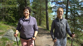 Two active women do Nordic walking in Park. Tracking shot. stock footage