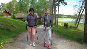 Two active women do Nordic walking in the Park. Tracking shot. stock video