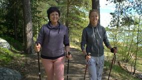 Two active women do Nordic walking in Park. Tracking shot. Slow motion. stock video