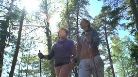 Two active women do Nordic walking in Park. Tracking shot. Slow motion. stock video footage
