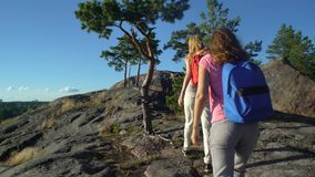Two Active Young Women Help Each Other to Climb a High Rock. Two active young women with backpacks are climbing cliff. Friends help each other to climb the high stock footage