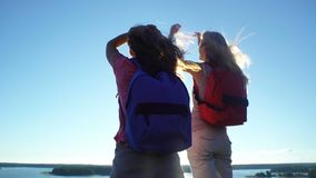 Two Active Young Women Help Each Other to Climb a High Rock. Two active young women with backpacks are climbing cliff. Friends help each other to climb the high stock video