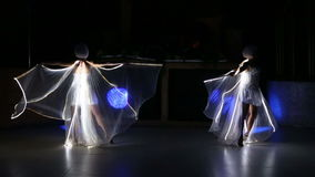 Two actress girl in white. Two beautiful actress girl in white clothes and unusual white wigs dancing with LED wings that glow on the stage under the floodlights stock video
