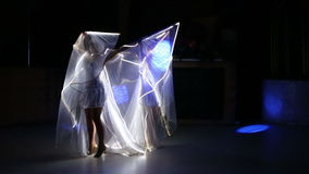 Two actress girl in white. Two beautiful actress girl in white clothes and unusual white wigs dancing with LED wings that glow on the stage under the floodlights stock footage