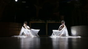 Two actress girl in white. Two beautiful actress girl in white clothes and unusual white wigs dancing with LED wings that glow on the stage under the floodlights stock video footage