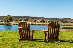 Two Adirondack Chairs Before a Rural Lake. Two Adirondack chairs before a lake in a mountainous valley in San Diego, California Royalty Free Stock Photography