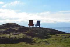 Two adirondack chairs. Two adirondack, rustic wooden chairs placed side by side on a hillock with view of distant plain, blue sky and cloud royalty free stock image