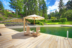 Two adirondack wooden chairs with umbrella on dock facing beautiful landscape. Royalty Free Stock Photo