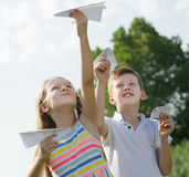 Two admiring kids playing with simple paper planes. On sunny day Stock Photography