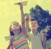 Two admiring kids playing with simple paper planes. On sunny day Royalty Free Stock Photo