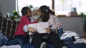 Grandchildren kissing grandfather with xmas gift stock footage