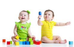 Two adorable babies playing with toys. Toddlers royalty free stock images