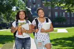 Two female college students on campus with backpacks and books Royalty Free Stock Image