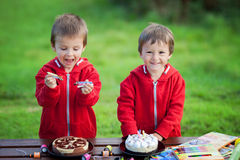 Two adorable boys with cakes, outdoor, celebrating birthday Stock Image
