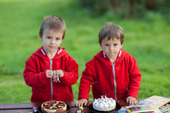 Two adorable boys with cakes, outdoor, celebrating birthday Royalty Free Stock Image