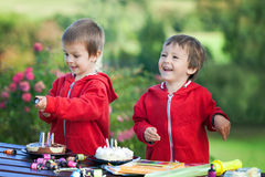 Two adorable boys with cakes, outdoor, celebrating birthday Royalty Free Stock Images