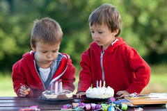 Two adorable boys with cakes, outdoor, celebrating birthday Stock Photography