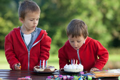 Two adorable boys with cakes, outdoor, celebrating birthday Royalty Free Stock Photography