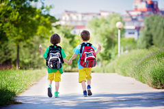Two adorable boys in colorful clothes and backpacks, walking awa Royalty Free Stock Photos
