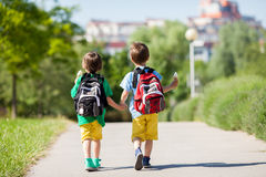 Two adorable boys in colorful clothes and backpacks, walking awa Stock Images