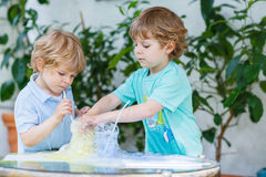 Two adorable boys making experiment with colorful bubbles. Two adorable preschool boys playing, having fun and making experiment with colorful soap bubbles and royalty free stock images