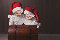 Two adorable boys, opening wooden chest, glowing light from insi Royalty Free Stock Photos