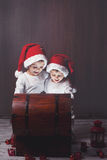 Two adorable boys, opening wooden chest, glowing light Stock Photography