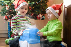 Two adorable boys playing with working humidifier, waiting for x-mas.  Royalty Free Stock Photo