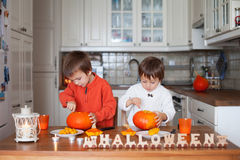 Two adorable boys, preparing jack o lantern for Halloween Royalty Free Stock Photos