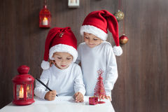 Two adorable boys, writing letter to Santa. At home Stock Images