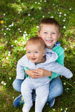 Two adorable brothers sitting on green grass Stock Images