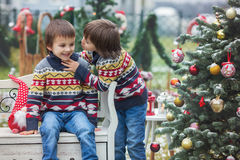 Two adorable children, boy brothers, having fun outdoors in the. Garden on Christmas around the decorated christmas tree while snowing outside Stock Photography