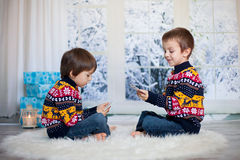 Two adorable children, boy brothers, playing cards at home, wint Royalty Free Stock Image