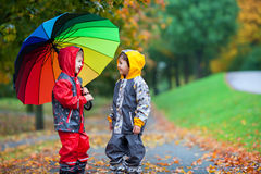 Two adorable children, boy brothers, playing in park with umbrel. Two adorable children, boy brothers, playing in park with colorful rainbow umbrella on a rainy stock photos