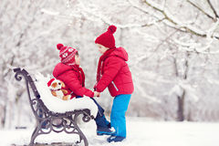 Two adorable children, boy brothers, playing in a snowy park, ho Royalty Free Stock Photo