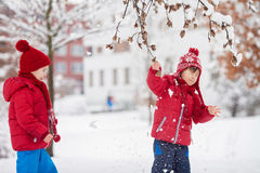 Two adorable children, boy brothers, playing in a snowy park, ho Royalty Free Stock Photos