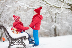 Two adorable children, boy brothers, playing in a snowy park, ho Royalty Free Stock Image